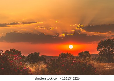 Sunset forming light rays over Portugal and the Guadiana River seen from Costa Esuri, Ayamonte, Spain. The colours are reminiscent of the gold and red bands of the Spanish flag