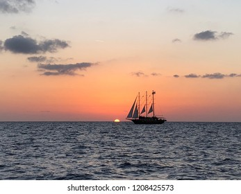 Sunset in front of an old-fashioned tall ship. Sunset cruise in Santorini, Greece.