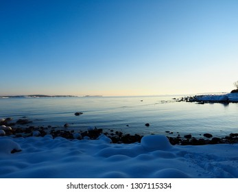 Sunset at frozen beach with fresh snow cover at winter, blue water and clear blue sky