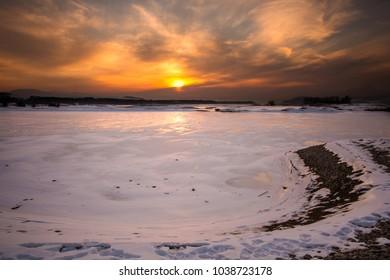Sunset at frozen lake
