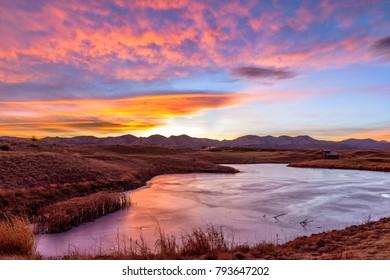 Sunset Frozen Mountain Lake  - A colorful winter sunset view at a frozen mountain lake. Bear Creek Park, Denver-Lakewood, Colorado, USA.