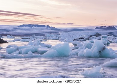Sunset in the glacial lagoon. Floating on the water ice pieces and a beautiful sunset sky. Long exposure. Iceland. Country of ice and fire.