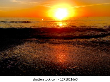 Sunset glimmer on sand and sea