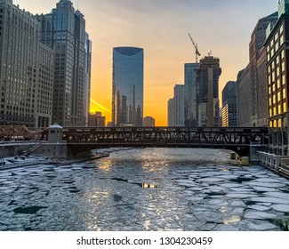 Sunset glow reflects off of windows of skyscrapers and ice on the surface of an icy Chicago River during winter evening