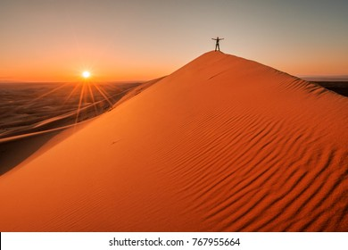 Sunset at Gobi desert, huge dunes with standing woman, Mongolia
