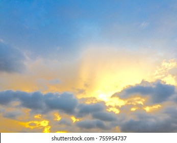 Sunset with gold sunlight and blue sky white clouds, sun rays beautiful light on spring season