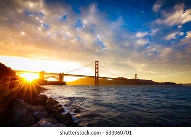 Sunset at the Golden Gate Bridge with sun starburst, San Francisco, California