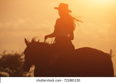Sunset golden silhouette of young cowgirl in hat riding her horse