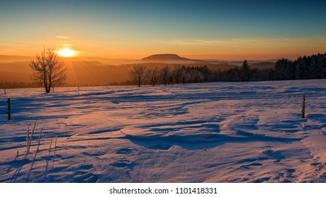 "Sunset in the golden sunlight over the winterly Ore Mountains. View to the mountain ""Scheibenberg"", mountain ""Fichtelberg"" and mountain ""Keilberg"""