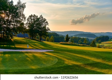 Sunset and golf course with flag, Europe. Czech Republic.
