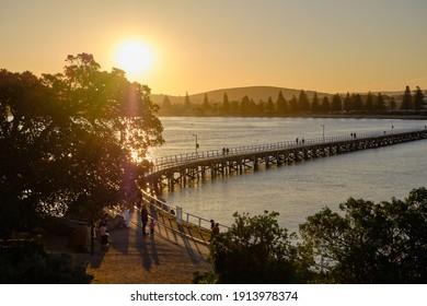 Sunset at Granite Island Heritage Causeway, people walking over the bridge, old horse drawn tram, orange and yellow vivid colors. Granite Island, Victor Harbor, South Australia