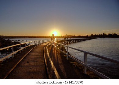 Sunset at Granite Island Heritage Causeway, old horse drawn tram, sun hiding behind hills, orange and yellow vivid colors, people walking over bridge. Granite Island, Victor Harbor, South Australia