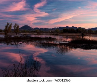 Sunset at the Gray Lodge Wildlife area, Pennington, California, USA,  featuring pink colors and reflections in the water, and the Sutter Buttes in the background