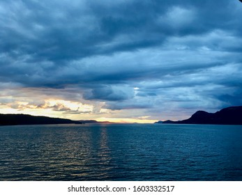 Sunset in the Gulf Islands in the Salish Sea in British Columbia, Canada.  Dark blue and grey clouds cover the sky with the sun peaking out in areas.