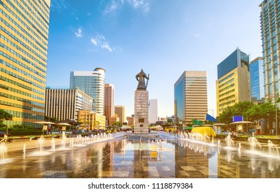 Sunset of Gwanghwamun Plaza with the statue of the Admiral Yi Sun-sin and modern buildings in downtown Seoul,South Korea.