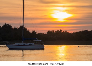 Sunset in the Harbor. The sky lights up with color and provides a source for reflection and serenity. Taken in the historic city of Beaufort North Carolina, USA. Sailboats sit quietly in calm waters.