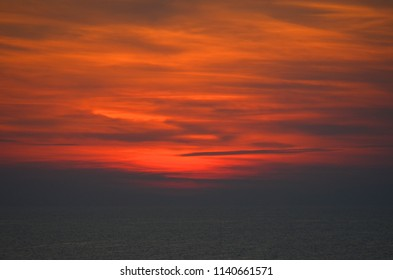 Sunset has turned the sky orange, patterned with dark clouds. Below the clouds, a dark sea can just be seen.