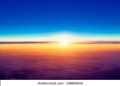 sunset with a height of 10 000 km. Dramatic sunset. View of sunset above clouds from airplane window