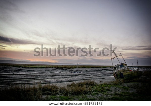 Sunset at Heswall boat yard Wirrl UK - old wrecks decay on the shoreline of the Dee estuary