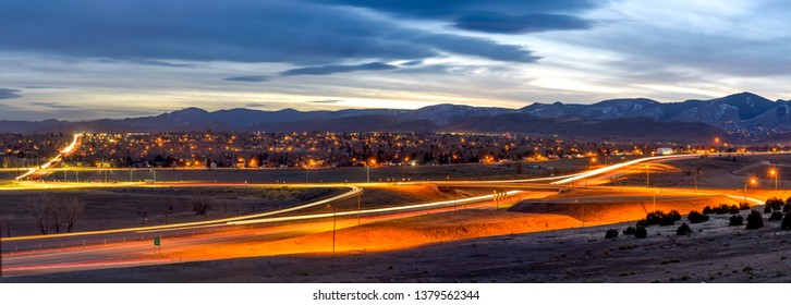 Sunset Highway - A panoramic dusk view of U.S. Highway 285 winding at the foothill of Front Range of Rocky Mountains on a stormy winter evening. Southwest of Denver, Colorado, USA.