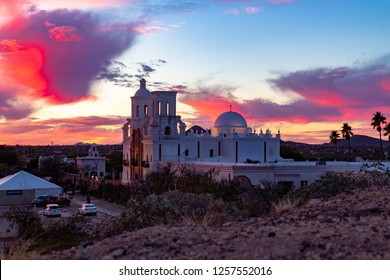 Sunset at the historic Mission San Xavier del Bac near Tucson, Arizona. Beautiful view from hill east of building. Colorful sky with red, orange, purple pink and blue colors in the clouds. USA 2018.