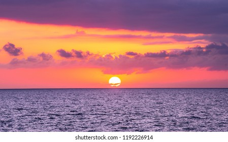 Sunset in holiday paradise resort on Grand Comore island, Comoros. Beautiful sunset light of sun going into the sea. Villas on the beach with private beach. Moroni Comoros. Purple blue and orange red