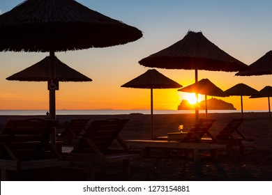 Sunset in holiday resort on Turkish coast with umbrellas on beach. Calm blue sky and orange Sun over low horizon