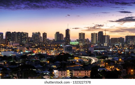 Sunset in Honolulu, over Waikiki beach and hotels, as the sun dips into the horizon at golden hour