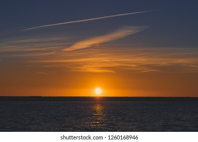 Sunset horizon over the sea water landscape, with a view of the sun setting in the afternoon