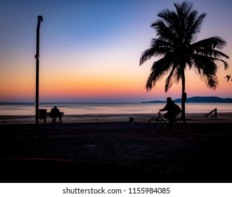 Sunset Hour at Meia Praia Beach in Itapema Santa Catarina with a person on the bench and a bicycle rides.