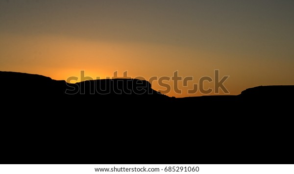 Sunset hues behind mountain silhouette