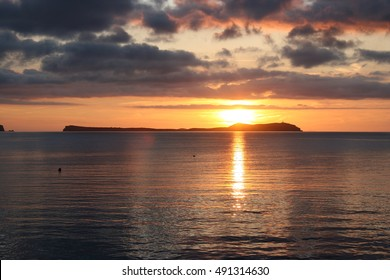 sunset in Ibiza,dawn in Ibiza,with some clouds on the horizon, golden yellow sun and golden sun wake in the sea, a calm Mediterranean Sea,