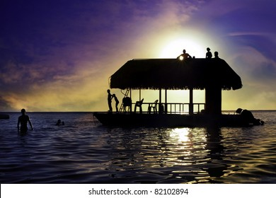 Sunset image with silhouette of boat and children playing.