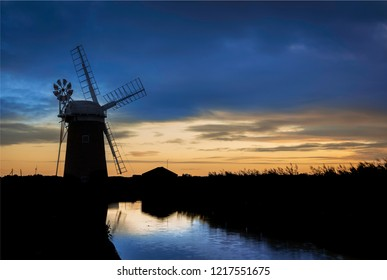 Sunset image of a silhouetted Wind Pump. Not a windmill, but a wind powered pump traditionally used for pumping water off the fields and into the Norfolk Broads. Blue sky with orange glow of sunset.
