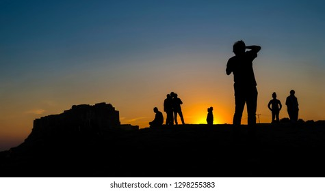 Sunset in India with silhouette of tourists