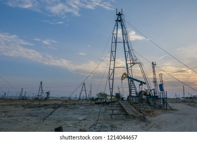 Sunset industrial landscape, petroleum industry and oil pumps