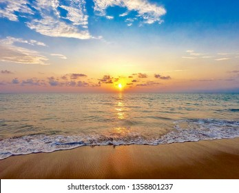 Sunset into the sea with wave,horizon, blue and gold sky
