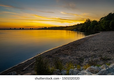Sunset at Johnson's Beach Barrie Ontario with lake view, light, cloud, trees, stones, and sand