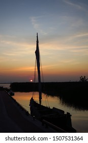 Sunset in Kintai, small fishing village in Lithuania near Curonian lagoon, with view to Curonian spit, dead dunes and the boat
