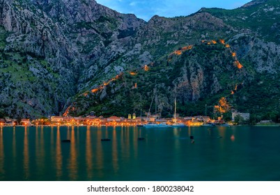 Sunset of Kotor Bay or Boka Kotorska with an illuminated ancient fortress city wall in the mountains, the Balkans, Montenegro on the Adriatic Sea
