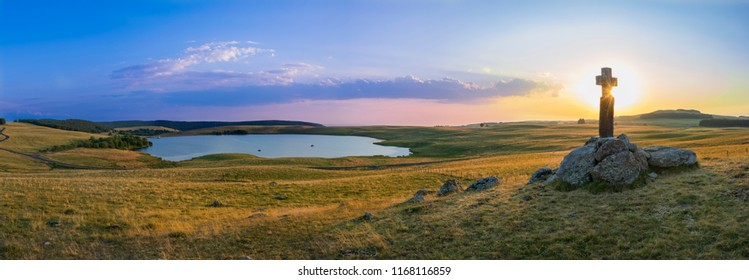 Sunset in lake of monks in Aubrac - France- with a stone cross