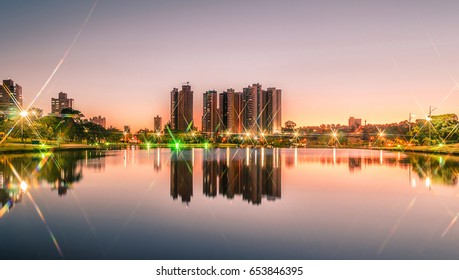 Sunset at a lake of a park with the city on background. Scene reflected on water. Landscape of a beautiful warm sunset at Parque das Nacoes Indigenas in Campo Grande, Brazil.