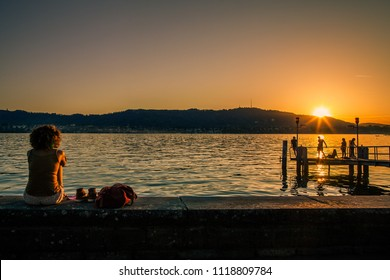 Sunset at lake promenade at Lake Zurich. The lake promenade is a popular place to enjoy sunshine