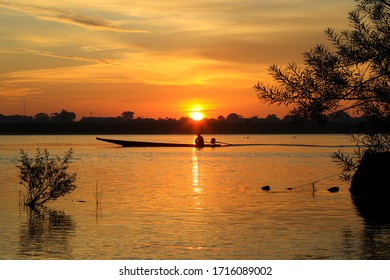 Sunset at Lake with silhouettes small fishing boat on foreground,select focus with shallow depth of field.Orange color reflection in the water surface