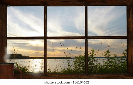 Sunset at the lake in summer, as seen through the cottage window, with a steaming cup of coffee sitting on the windowsill.  Part of a series.