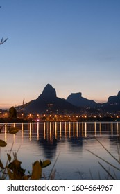 Sunset from the lakeside edge of Lagoa Rodrigo de Freitas in Rio de Janeiro, with clear blue sky and orange street lights. Dois Irmaos Mountain and Pedra da Gavea are reflected in the calm lake water.