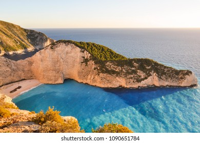 Sunset landscape from above on the most famous, vacation summer beach and bay in the world - Navagio on Zakynthos Island in Greece. Top view from rock cliff on blue sea and beach with old shipwreck.