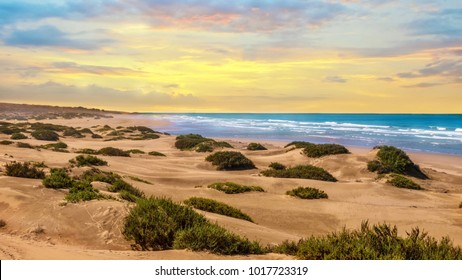 Sunset landscape in Agadir, Morocco, where desert sand turns into a beach at the Atlantic Ocean.
