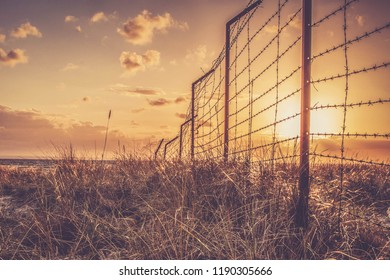 sunset landscape behind a metal military fence in the dunes and beach