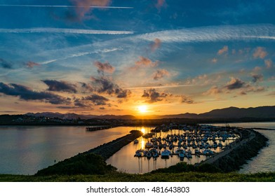 Sunset landscape of coastal city with dramatic clouds and plane trails on the background. Muttonbird Island Nature Reserve, Coffs Harbour, Australia